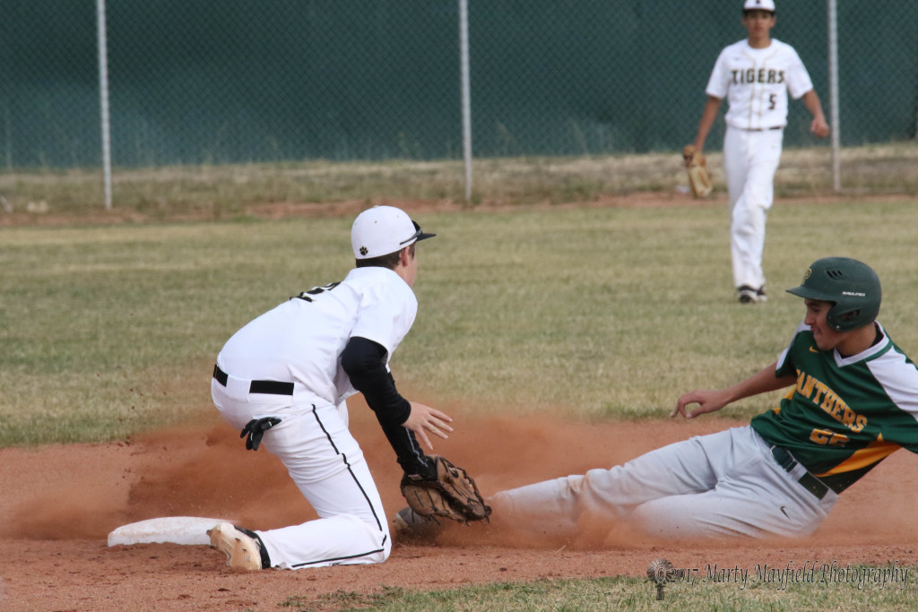 Safe at Second calls the umpire as Jason Parker goes for the tag on Cameron Quintana Tuesday afternoon during the first district game of the season