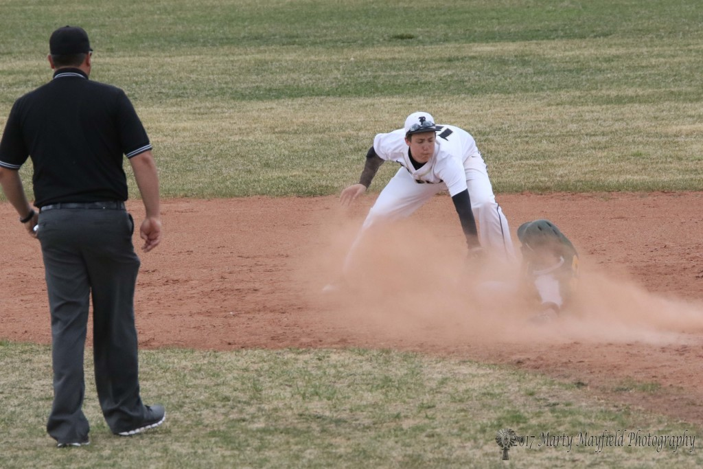 Jason Parker makes the tag as Cameron Quintana slides in a cloud of dust into second base during the first district game of the season