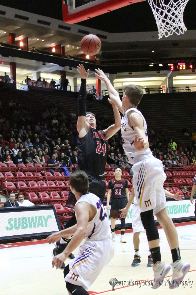 Isaiah Garcia takes the shot as Kolton Riggs attempts the block, Garcia put in 12 points for the Red Devils.