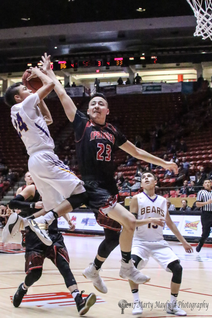 Estevan Romero flies by Andrew Archuleta who holds up his shot just long enough for romero to clear and puts it in for another two during the state title game in Albuquerque Saturday morning.