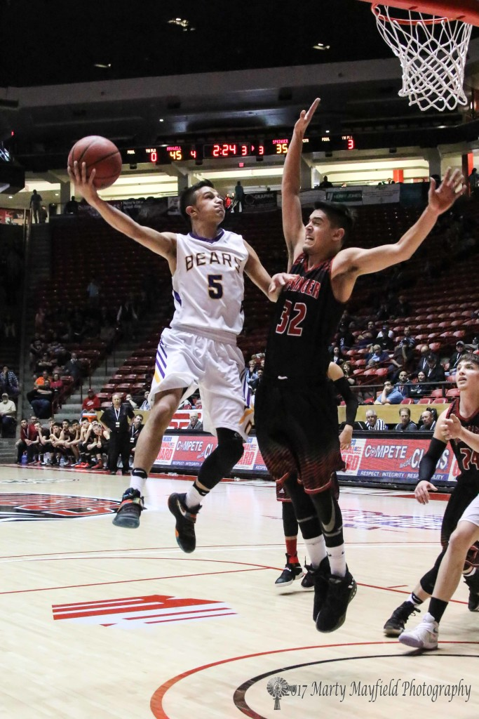 Zac Caldwell (32) goes up for the block as Carl Gonzales (5) takes the hook shot late in the third quarter of the state title game Saturday in Wise Pies Arena