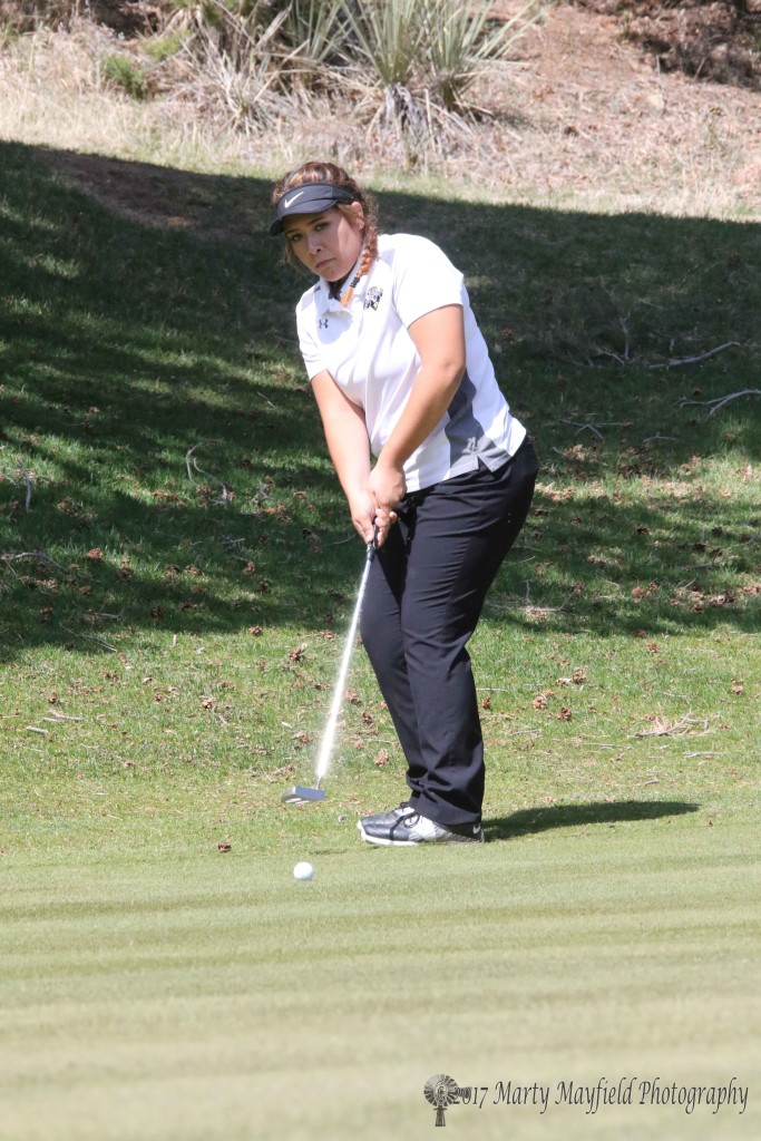 Sydni Silva works the putt from the edge of the number two green on her way to a first place finish in the first ever Red Devil Golf Tourney held at the Raton Golf course Monday
