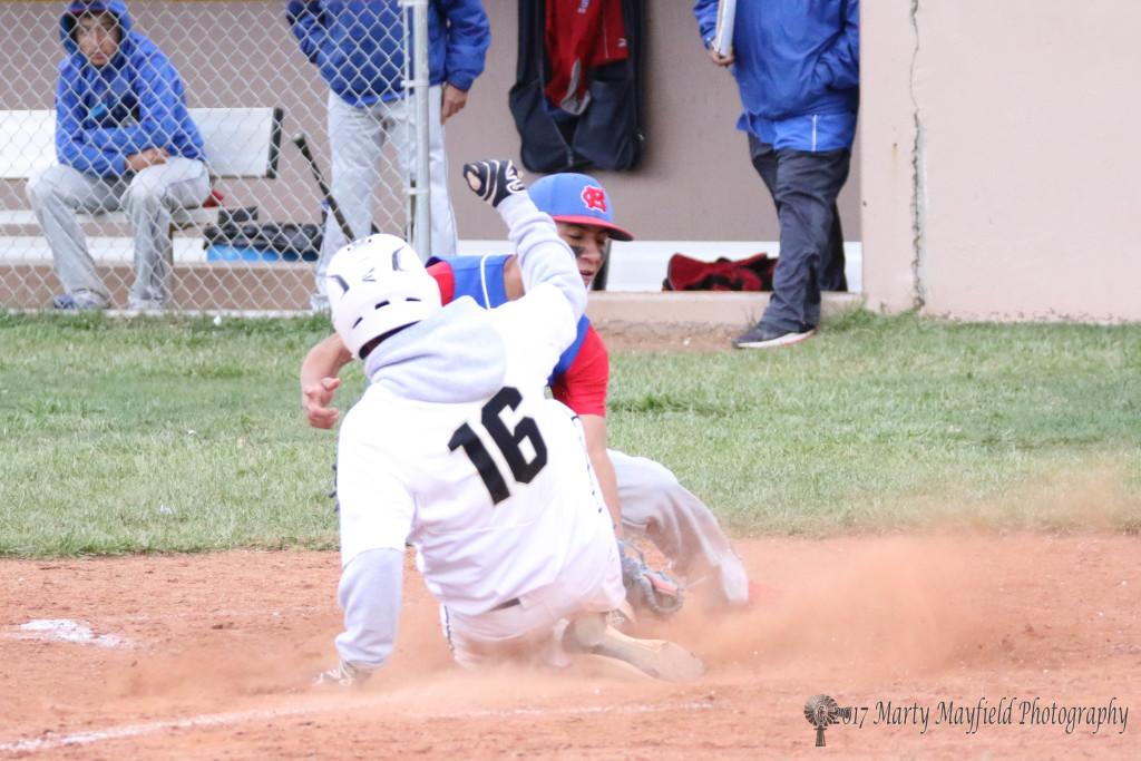 In a cloud of dust Richie Gonzales makes the slide safe into home plate Saturday afternoon against McCurdy