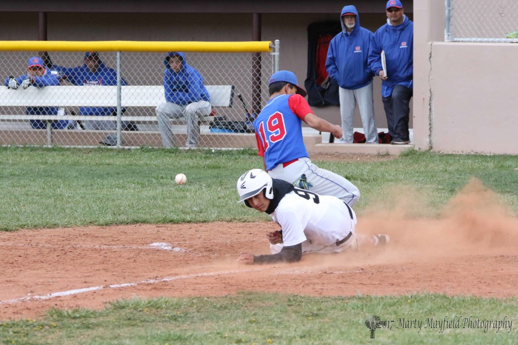 Gabe Martinez adds another run to the board as he slides in under pitcher AJ Vallo Saturday afternoon in the district game with McCurdy.