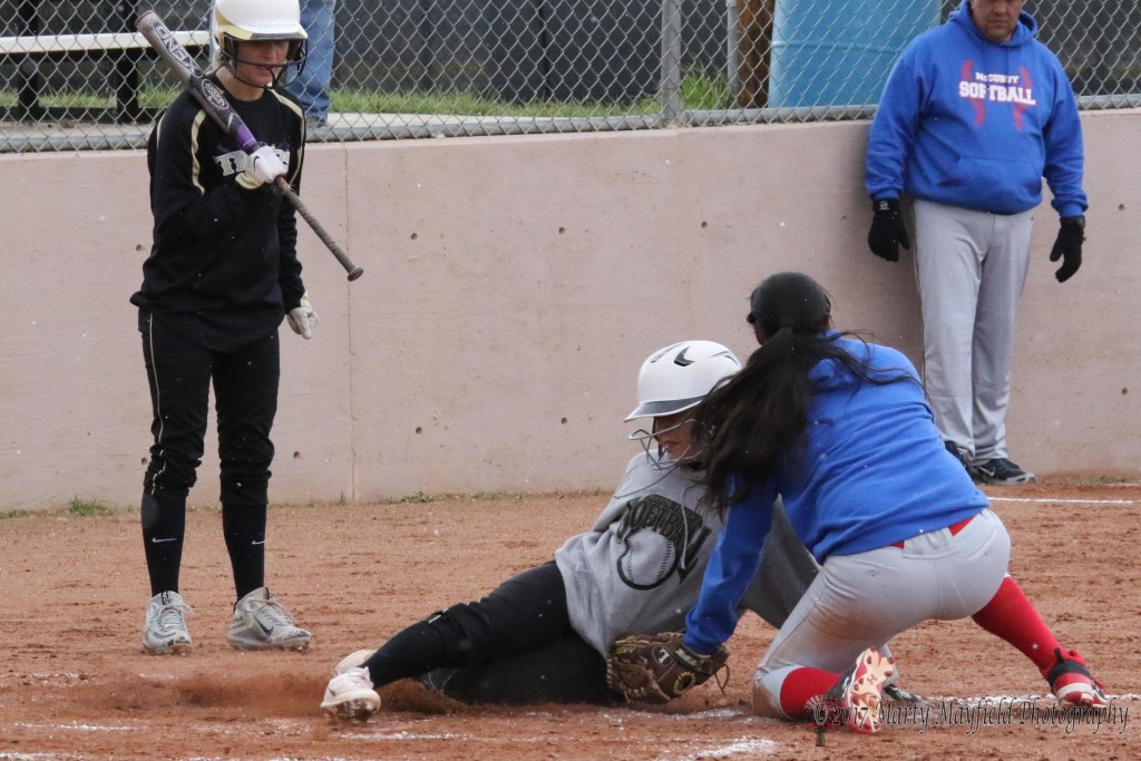 In a close one at home plate Alexi Romero slides into home plate and but the call is out as the McCurdy pitcher makes the tag.