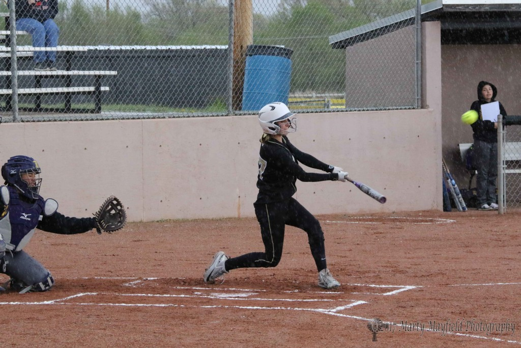 Camryn Mileta makes contact ands sends the ball sailing into left center field Tuesday afternoon before  the skies open up and cancel the rest of the game with Tucumcari