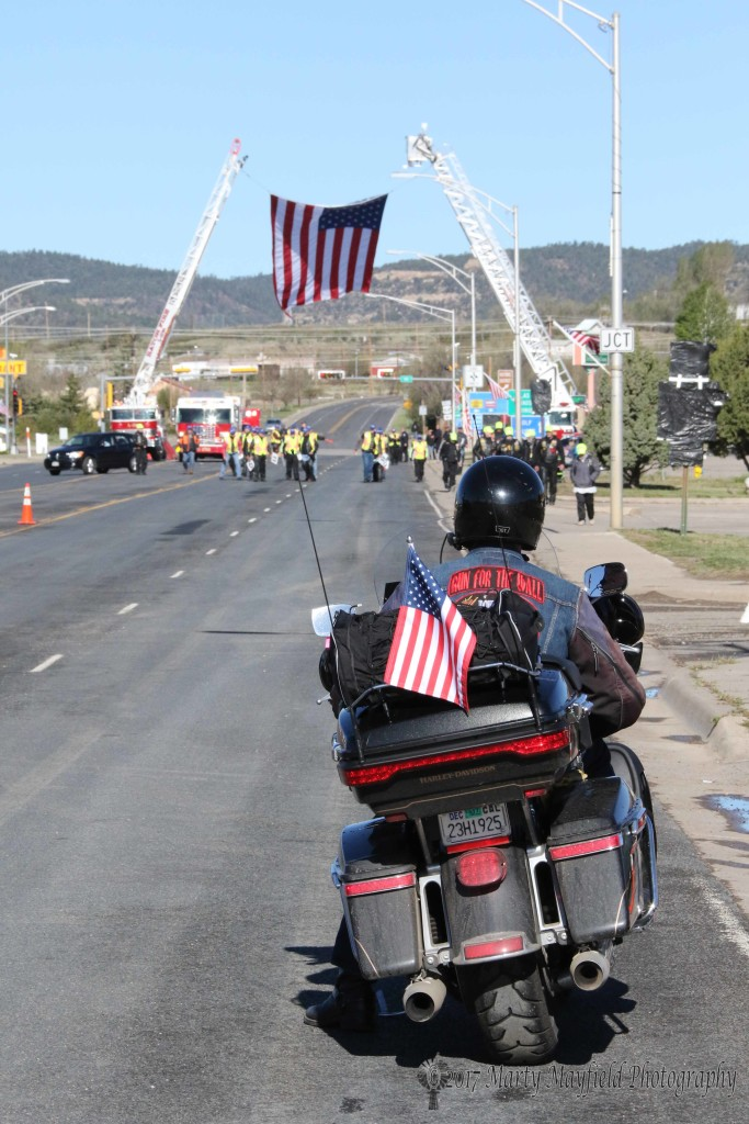 A Run for the Wall rider watches the US Flag wave in the breeze over Clayton Road
