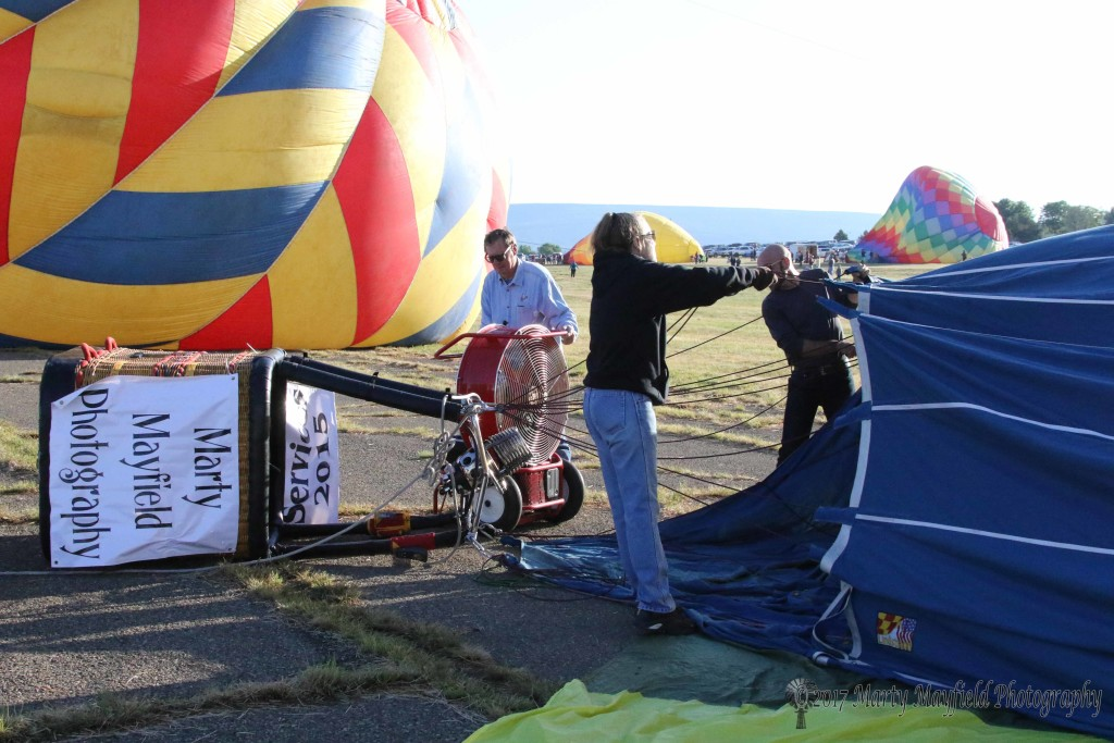 Pilot Gerry Graff cold packs the balloon with the big fan Sunday morning as the rally began with mostly clear skies.