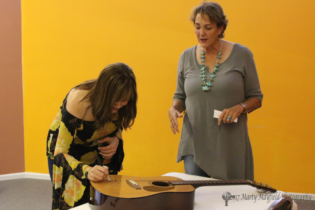 Wendy Hickman watches as Suzy Bogguss signs the guitar that she won in a contest for the 3rd Annual Gate City Music Festival held over the Labor Day weekend.
