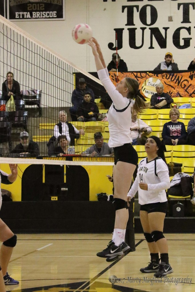 Ginger Baird tips one back over the net during the JV match with Desert Academy Thursday evening in Tiger Gym.