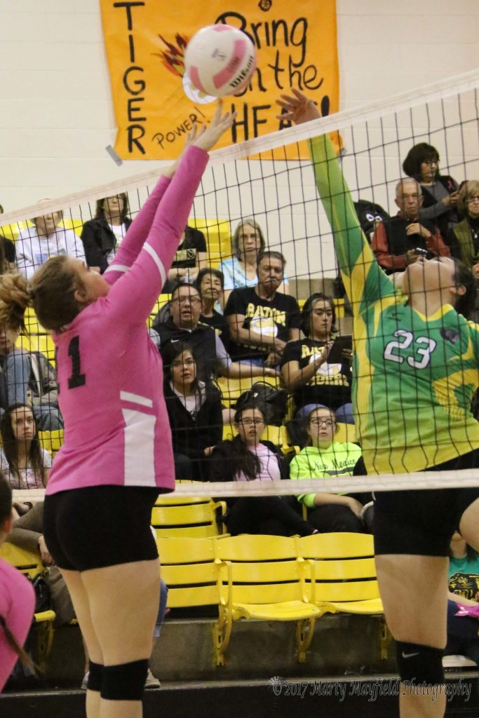 Kerrigan Weese goes up for the block but only gets a finger on the spike by Reyna Perez during the second game of the match with Pecos.