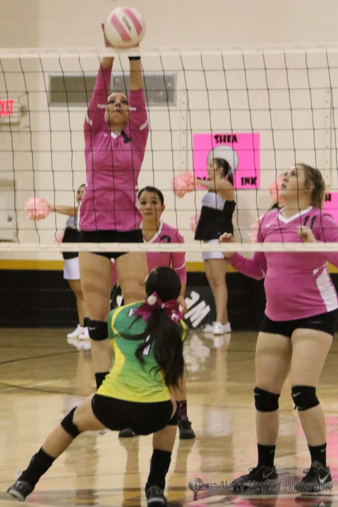 Camryn Mileta gets the block as Trinity Herrera watches her hit come back over the net Saturday afternoon in Tiger Gym.