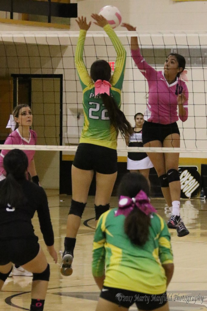 Autumn Archuleta slams one over the net as Faith Flores goes up for the block Saturday afternoon in game 3 of the district match with Pecos.