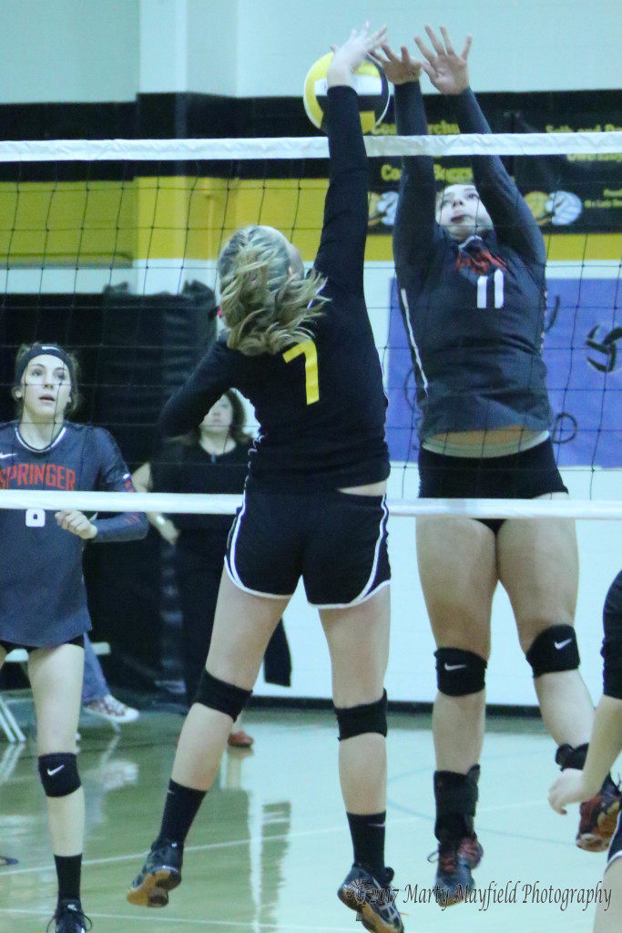 Natashia McDonald(7) and Katy Scott(11) meet at the net during the District 1A Championship match in Des Moines Saturday evening.