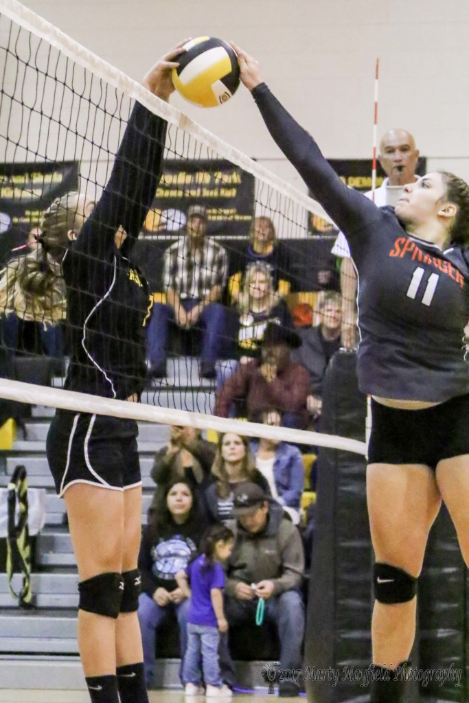 Katy Scott and Natashia McDonald meet at the net during the District Championship Match in Des Moines Saturday evening.