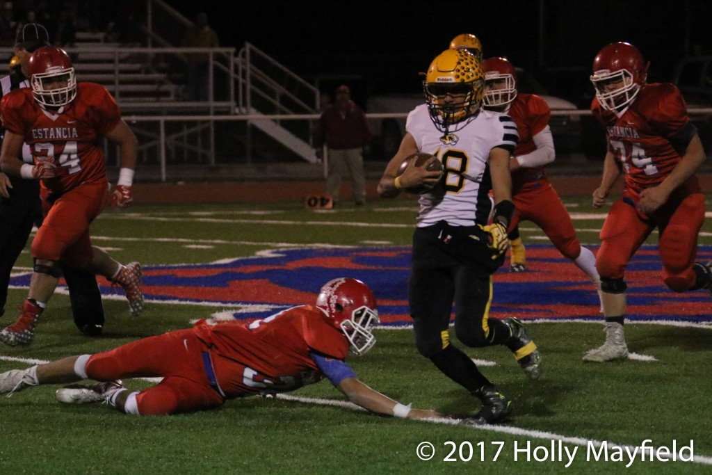 The elusive Dustin Segura gets around this would be tackler for a good gain Friday night during the state playoff game in Estancia.