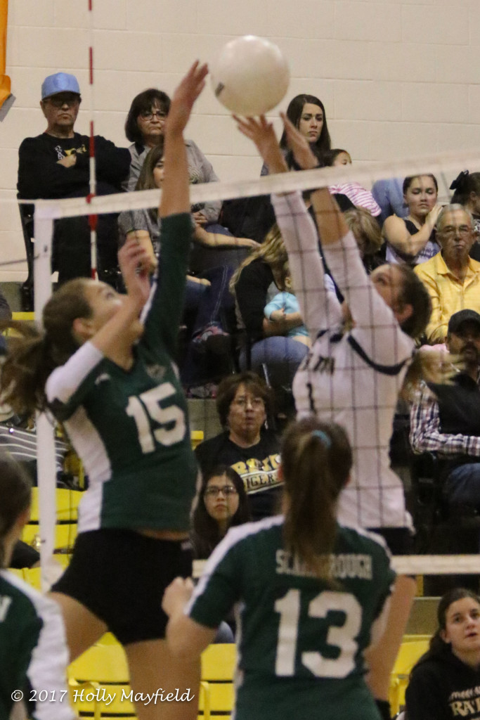 Michaela Glinsky (15) meets Camryn Mileta at the net a scene that played out several times during the district match Friday night in Tiger Gym.