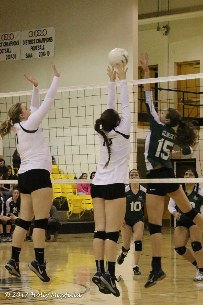 Michaela Glinsky tips the ball up and over with Autumn Archuleta and kerrigan Weese going up for the block Friday night during the District Championship match in Tiger Gym.