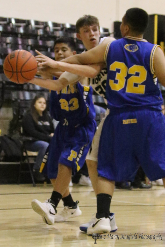 Raton's Reyes Aragon gets caught in the squeeze as Jerome Lopez(23) and Angelo Sanchez(32) move in to steal the ball during the JV game Tuesday evening in Tiger Gym.