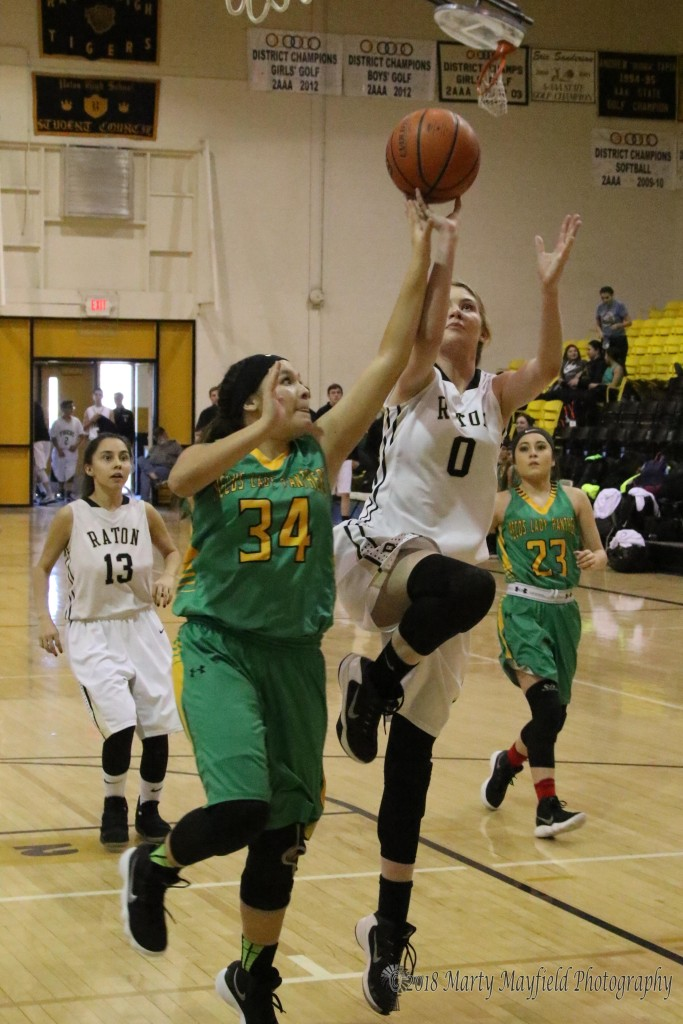Dominique Salinas (34) goes up with Ginger Baird (0) as she drives the lane for the shot during the district game with Pecos Saturday afternoon.