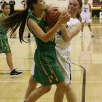 Jadyn Walton and Faith Flores struggle for the ball during the district game in Tiger Gym Saturday evening.