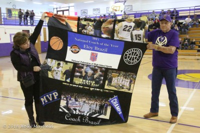 Linda Gallegos and Larry Menapace of the Maxwell Booster Club show off the blanket that was presented to Coach Brazil.