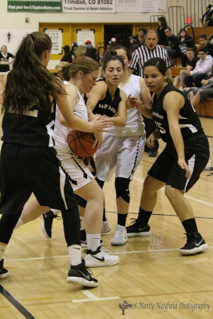 Jadyn Walton struggles for control of the ball with a host of Wild Wolves gathering around during the game Saturday afternoon in Tiger Gym.